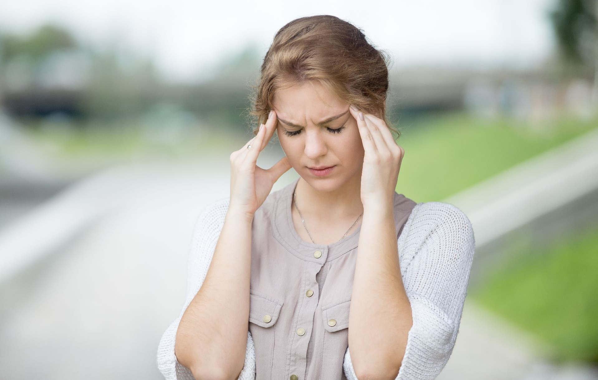 Portrait of stressed beautiful woman walking on the street and holding her head with hands trying to remember something or having headache. Attractive model suffering from pain outdoors in summer